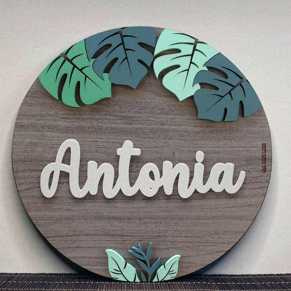 Placa circular de madera personalizada con nombre Antonia y figura de hojas monstera